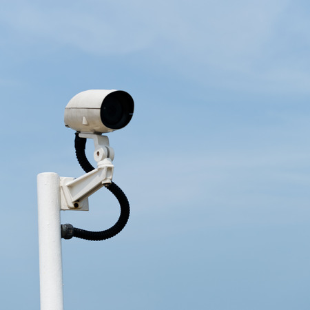 deterrent: CCTV security camera isolated on sky background.