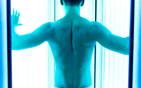 ultraviolet: Young muscular man at solarium. Stock Photo
