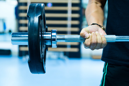 man lifting weights: Man with training equipment on sport gym Stock Photo