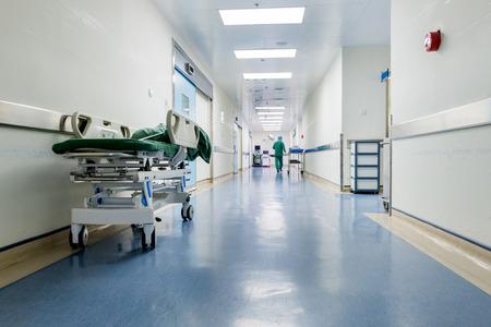 paciente en camilla: Los médicos y enfermeras caminando en el pasillo del hospital, confuso movimiento. Editorial