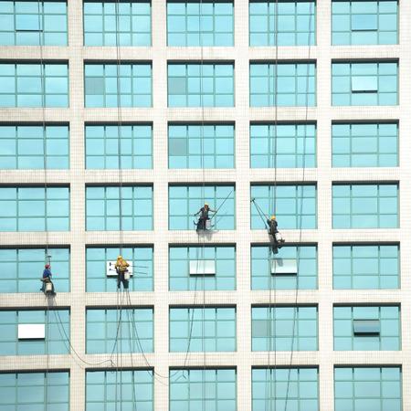 steeplejack: Workers of steeplejack washing windows of the modern building.