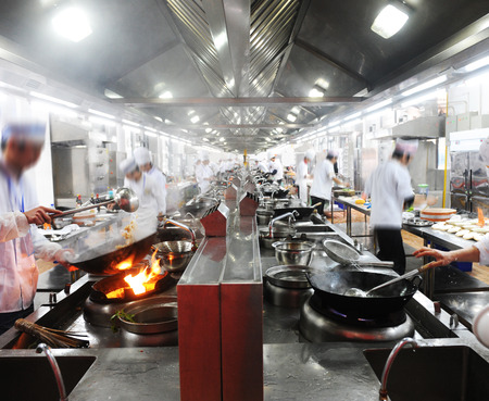 stainless steel pot: Motion chefs in a Chinese restaurant kitchen.