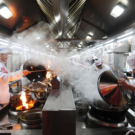 Fujian-April 14, 2010.  Group of chefs working together in a Chinese restaurant kitchen, Fujian province, China.  Reklamní fotografie - 37181498