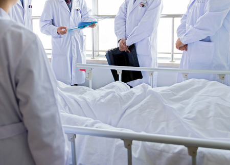 hospital patient: Medical team examining patient in hospital.  Stock Photo