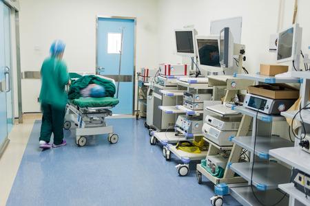 surgery stretcher: nurse walking in hospital hallway, blurred motion.