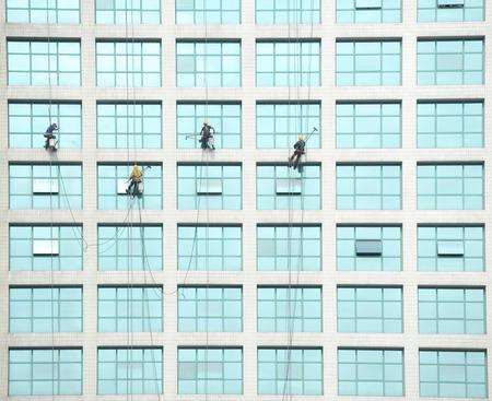 steeplejack: Workers of steeplejack washing windows of the modern building. Editorial