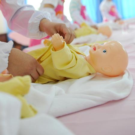 reanimate: newborn care exercise on infant dummy.