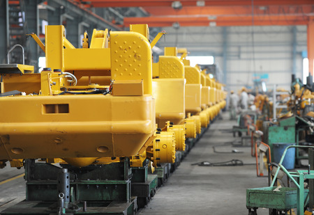 fila de personas: Taller de máquinas de producción de excavadoras. Foto de archivo