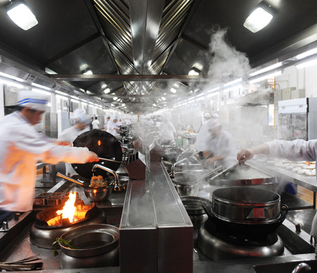 busy restaurant: Motion chefs in a Chinese restaurant kitchen. Editorial