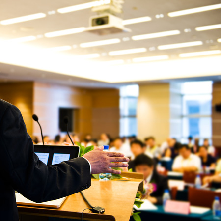 Business man making speech at a conference hall.