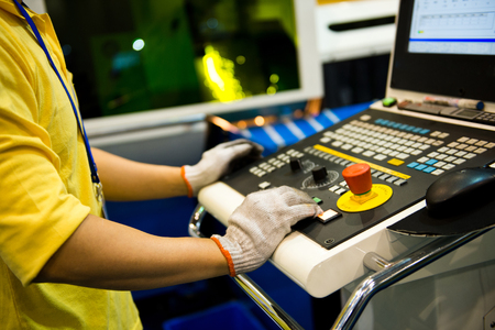 worker working with cnc machine at workshop.