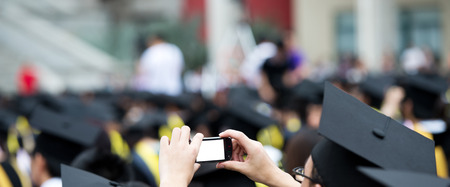 graduates taking photos by cellphone during commencement.