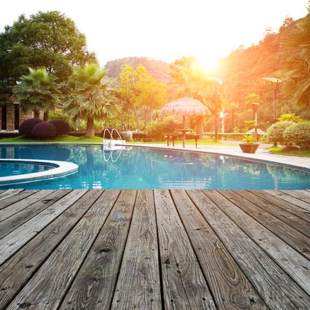 Wood platform beside swimming pool. Editorial