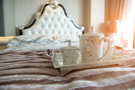 king size: luxury bedroom interior with beverage on bed.
