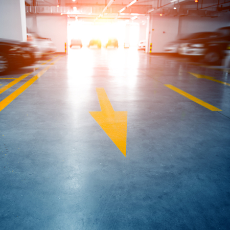 Empty underground garage with arrow leading to go to car park. Editorial