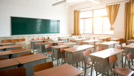 furnishings: Empty classroom with chairs, desks and chalkboard.