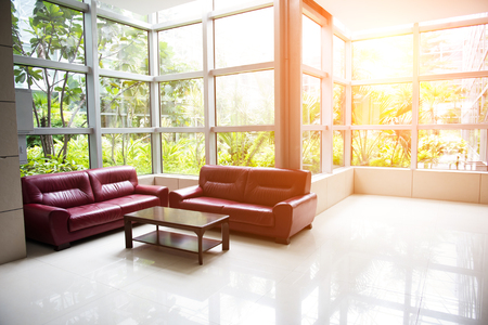 Sofá y mesa cerca de las ventanas en un moderno edificio de oficinas Foto de archivo - 75215466