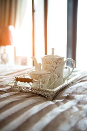 luxury bedroom interior with beverage on bed.