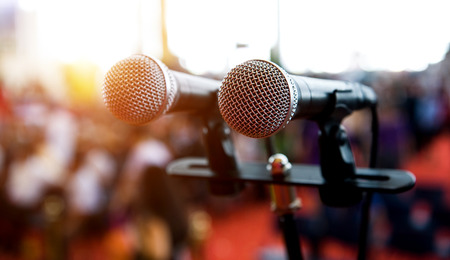 Closeup microphone in auditorium with people. Stock Photo