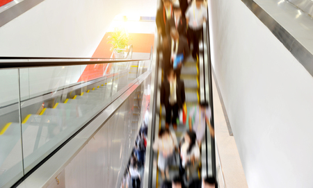 Business people walking on escalator.Blurred motion