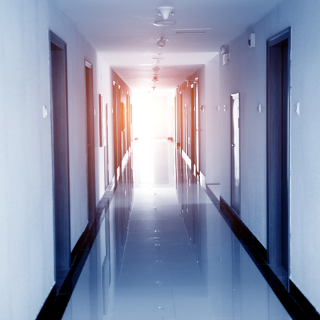 Empty long hotel corridor with doors. Editorial