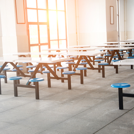 Pulizia scuola caffetteria con molti posti vuoti e le tabelle.