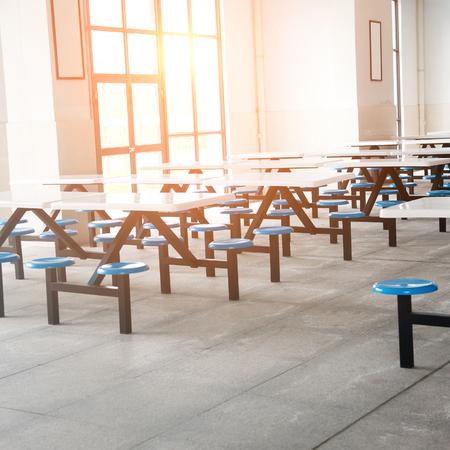 Schoon school cafetaria met veel lege stoelen en tafels.