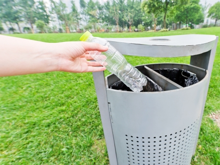 putting on: hand putting a plastic bottle into a recycling bin