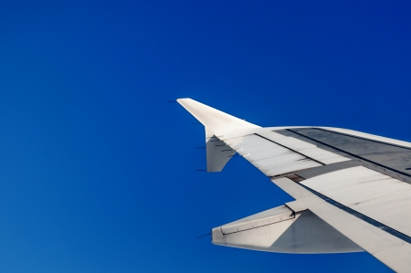 Wing of an airplane flying above the clouds  people looks at the sky from the window of the plane, using airtransport to travel  photo