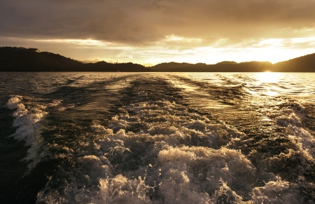 churning: Churning water in the ocean shows lots of turbulence and splash.sunset, Good for background image.
