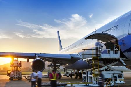 Avion à proximité du terminal dans un aéroport au coucher du soleil