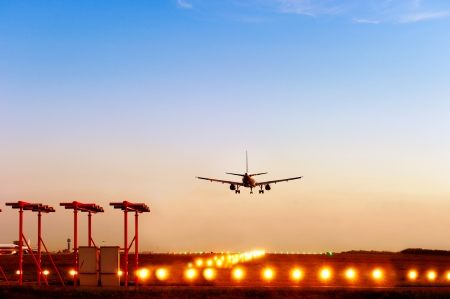 passenger plane fly down over take-off runway from airport at sunset