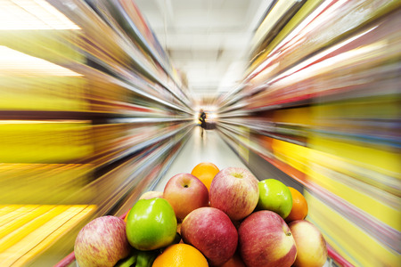 de focus: Supermarket interior, filled with the fruit of the shopping cart.