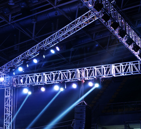 business equipment: Studio lighting equipment high above an outdoor theatrical performance.
