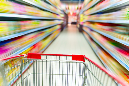 aisle: Supermarket interior, empty red shopping cart.