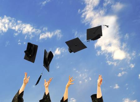 mortero: graduados tirando sombreros de graduación en el aire. Foto de archivo
