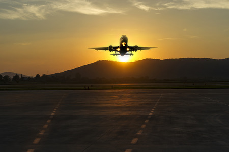 uprise: passenger plane fly up over take-off runway from airport at sunset
