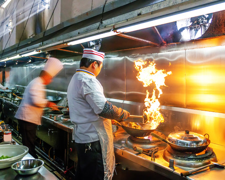 busy restaurant: Crowded kitchen, a narrow aisle, working chef.