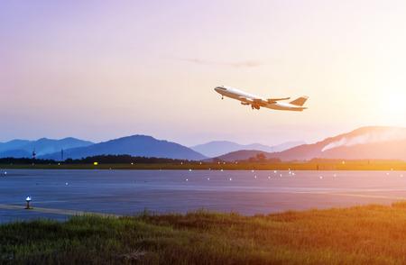 Passagierflugzeug fliegen bis über Take-off Piste vom Flughafen bei Sonnenuntergang  Lizenzfreie Bilder