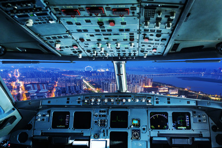 plane cockpit and city of night photo
