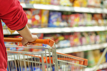Lady pushing a shopping cart in the supermarket. Zdjęcie Seryjne - 34990221