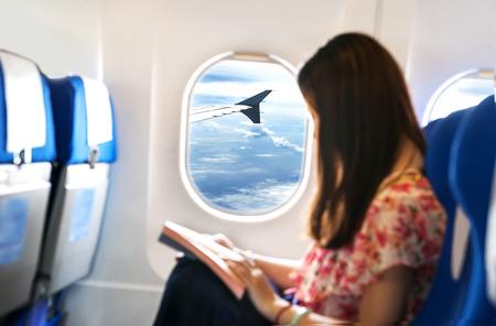 Mujer joven está en el asiento del pasajero en avión Foto de archivo - 35091420
