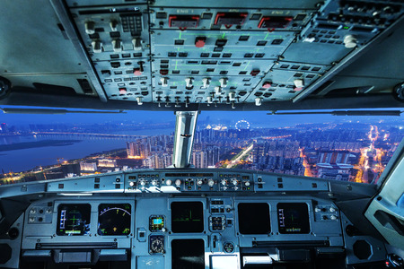 airplane landing: plane cockpit and city of night