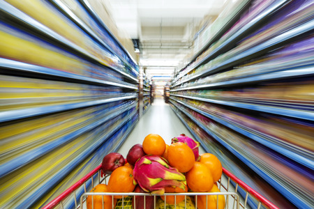 Image of cart full of products in supermarket photo