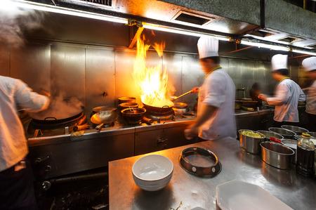 Overvolle keuken, een smalle gangen, werkende kok.