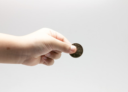 something: childs hand holding the coin