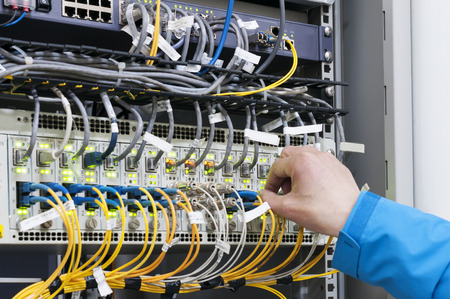 internet  broadband: Man connecting network cables to switches Stock Photo