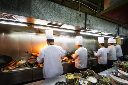 Crowded kitchen, a narrow aisle, working chef. Imagens - 35685625