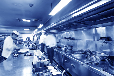 restaurant kitchen: Chef in restaurant kitchen at stove with pan, doing flambe on food
