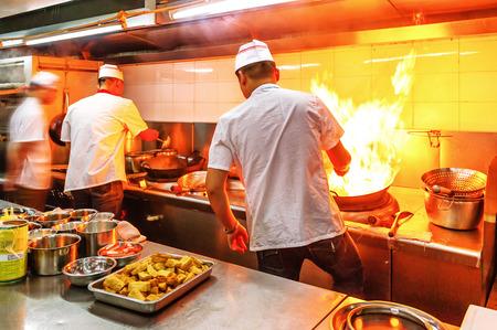 Chef-kok in de keuken van het restaurant op fornuis met pan, doet flambe op voedsel